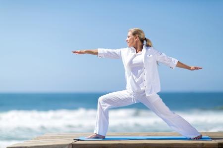 Photo pour pretty middle aged woman yoga pose by the beach - image libre de droit