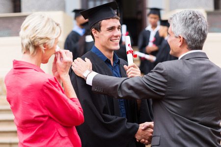 handsome male graduate being congratulated by his father at graduation ceremony