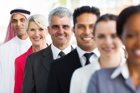 happy middle aged businesswoman standing in a row with business team