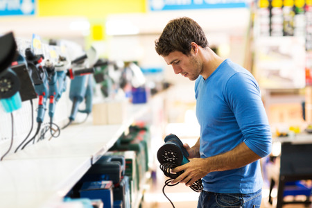 Photo pour handsome young man shopping for sander in hardware store - image libre de droit