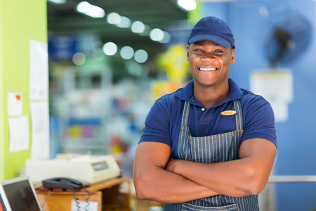 handsome african supermarket cashier standing at checkout