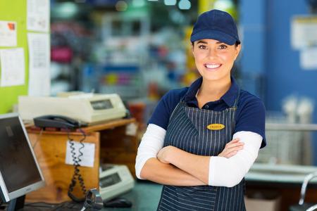 Photo pour happy female hardware store cashier with arms folded - image libre de droit