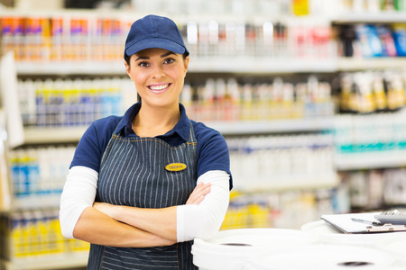 Photo pour beautiful young female supermarket worker with arms crossed - image libre de droit