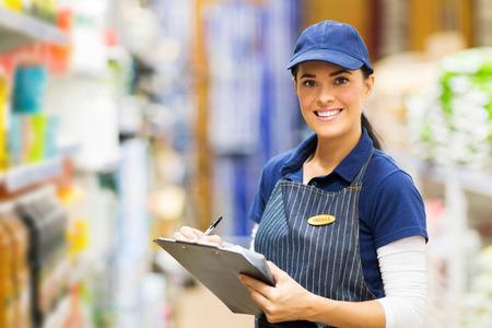 Photo pour happy female clerk working in supermarket - image libre de droit