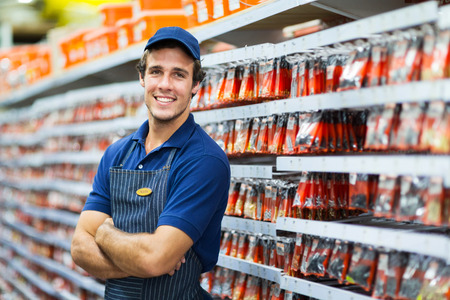Photo pour handsome hardware store salesman standing next to fasteners shelf - image libre de droit