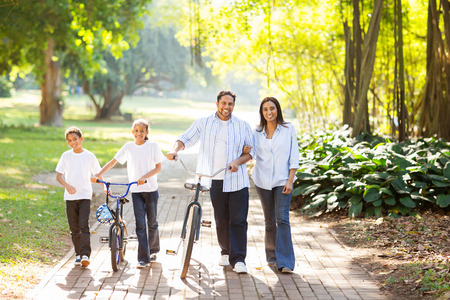 happy indian family of four walking outdoors in the park