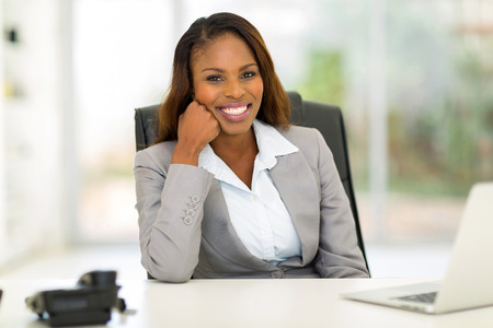 portrait of happy young african businesswoman sitting in office