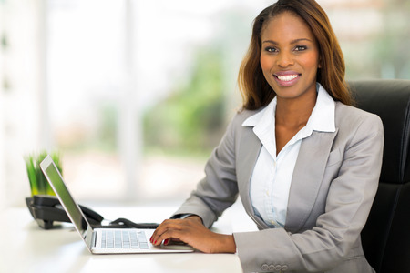 happy young african american businesswoman using computer in officeの写真素材