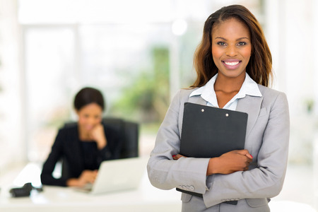 Photo pour black business woman holding clipboard with colleague on background - image libre de droit