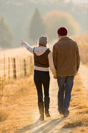Photo pour rear view of young couple walking in country road - image libre de droit