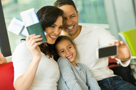 beautiful family taking selfie with smart phone while waiting for their flight at airport