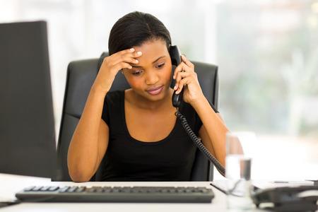 tired black businesswoman using landline phone in office