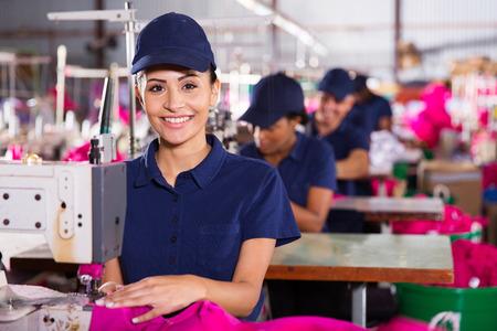 Foto de beautiful young textile machinist using sewing machine in clothing factory - Imagen libre de derechos