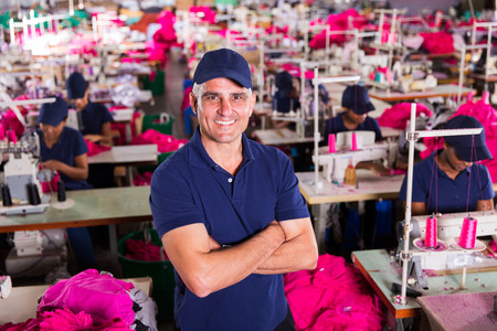 above view of senior clothing factory supervisor with arms crossed