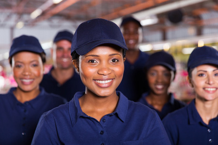 Photo pour happy young african factory worker with colleagues - image libre de droit