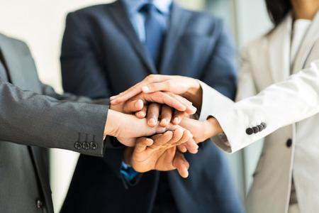 Foto de close up of multiracial business people putting their hands together, focus on hands - Imagen libre de derechos