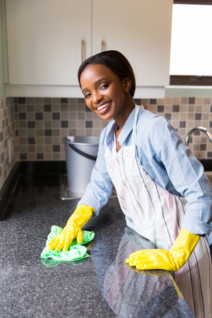 happy young african woman cleaning kitchen counter