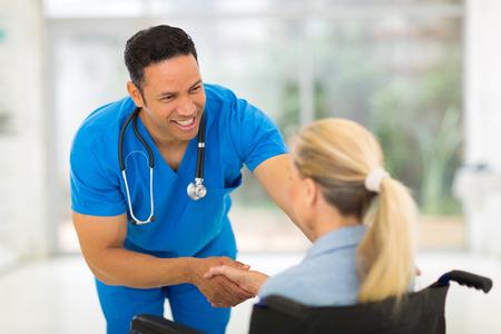 Photo pour friendly healthcare worker handshaking handicapped woman - image libre de droit