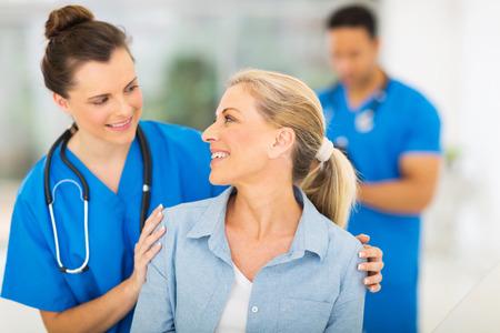 caring nurse talking to senior woman in hospital