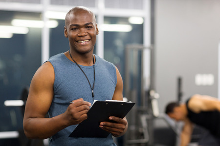 young african american male personal trainer holding clipboard in gym