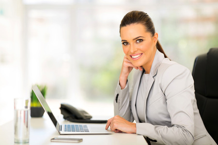 smiling business woman using laptop computerの写真素材