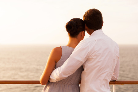 rear view of young couple on cruise vacation looking at the seaの写真素材
