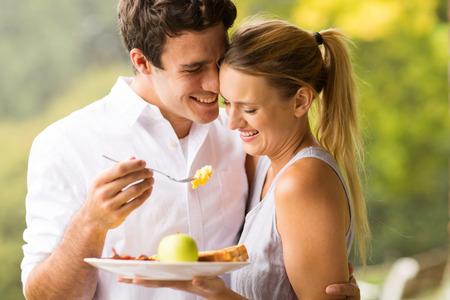 Photo pour loving husband feeding wife breakfast outdoors - image libre de droit