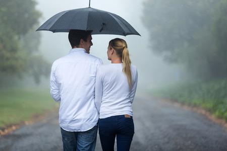 Foto de rear view of romantic couple walking in rain - Imagen libre de derechos