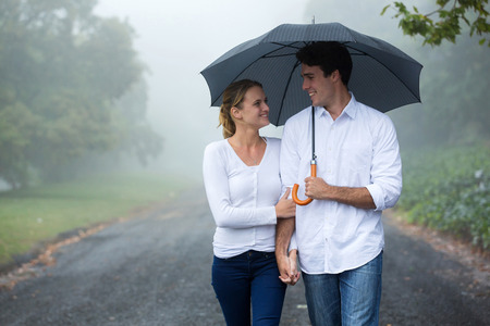 beautiful couple walking under umbrella in forestの写真素材