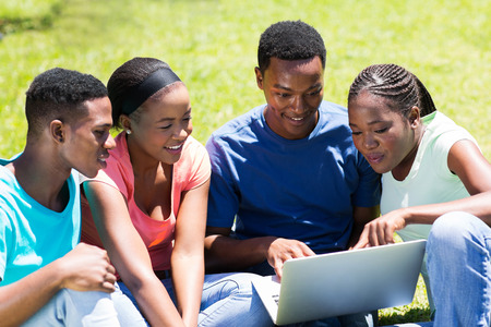 group of african university students using laptop outdoors