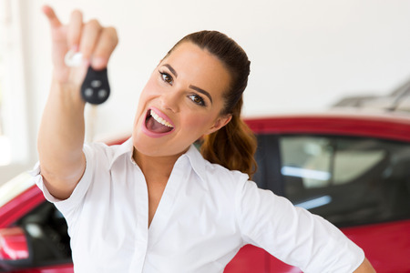 excited woman holding new car key at vehicle dealership