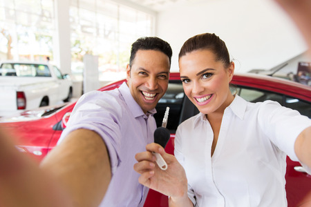 happy couple taking selfie together at dealership after bought new car