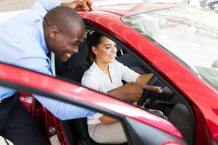 african salesman showing a new car to beautiful young woman
