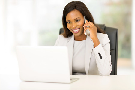 Foto de happy african american businesswoman talking on cell phone in the office - Imagen libre de derechos