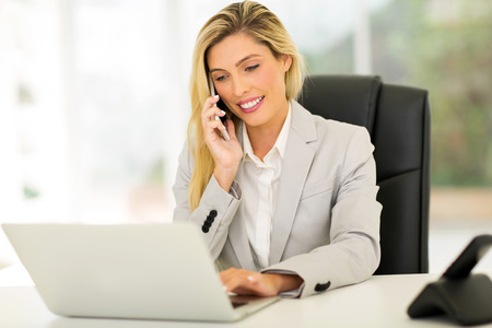 Happy Businesswoman Talking On Cell Phone In Office Royalty