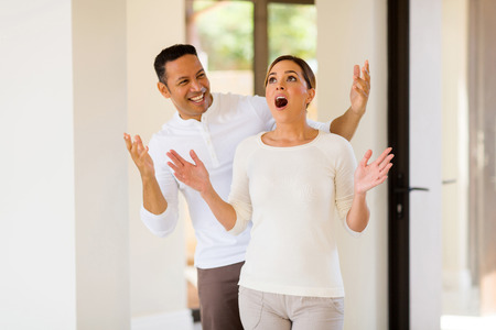 happy mid age man surprising his wife with a new house