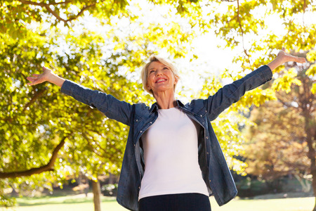 Photo pour low angle view of happy mid age woman with arms outstretched outdoors - image libre de droit