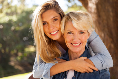 Photo for loving daughter hugging middle aged mother outdoors - Royalty Free Image