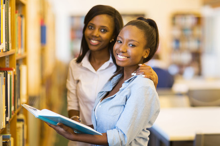 happy female african university students in libraryの写真素材