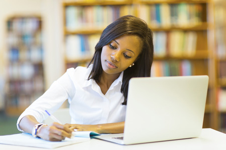 Photo for pretty female college student studying in library - Royalty Free Image