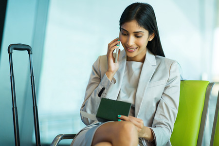 smiling young indian business woman talking on mobile phone while waiting for her flight at airport