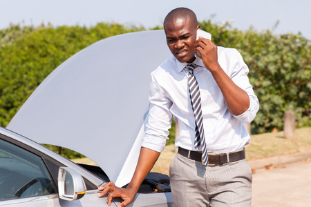 young african man calling for assistance with his car broken down by the roadside