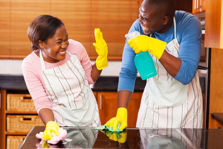 young african couple having fun while doing household choresの写真素材