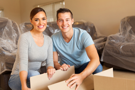 happy young couple unpacking boxes and moving into a new home