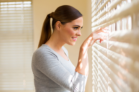 Photo pour beautiful woman peeking through window blinds - image libre de droit