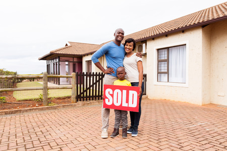 happy young african family in front of their home with sold real estate sign