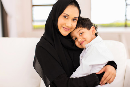 Photo pour attractive young muslim woman sitting on couch with her son - image libre de droit
