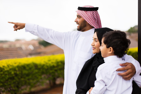 happy muslim family outside their home pointing