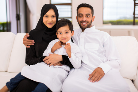 happy muslim family sitting on the couch at homeの写真素材