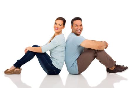 cute couple sitting back to back on white background